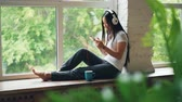 mensageiro : Cheerful Asian woman is listening to favourite song in headphones and using smartphone smiling and laughing sitting on window sill. Internet and youth culture concept.