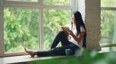 prazer : Attractive Asian girl student is reading book and smiling sitting on window ledge in modern apartment. Hobby, youth culture and interior concept. Stock Footage