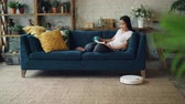 diário : Relaxed Asian woman is reading book turning pages sitting on couch at home when robotic hoover is cleaning floor doing housework. Leisure and technology concept.