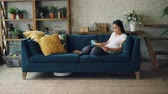 diário : Beautiful Asian girl is reading book resting on sofa in living room while robotic vacuum cleaner is dry cleaning floor and carpet. Technology and people concept.