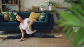 cabelos longos : Flexible Asian girl is doing yoga at home sitting on floor and stretching legs and body exercising alone. Beautiful room with furniture and plants is in background.