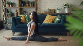 flexível : Female Asian gymnast is training at home practising splitting legs sitting on carpet in living room. Active lifestyle, flexibility and sporty young people concept. Vídeos
