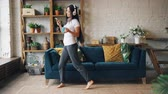 eğlenceli : Attractive Asian lady is listening to music in headphones, using smartphone and dancing on floor in living room holding device and cup of tea. People and leisure concept.