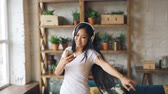 eğlenceli : Slow motion of happy Asian girl student wearing headphones and holding smartphone listening to music, dancing and enjoying leisure time. People and culture concept. Stok Video
