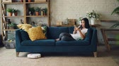 robótico : Attractive Asian girl is enjoying modern technology using smartphone and robotic vacuum cleaner sitting on sofa at home. Innovations and interiors concept.