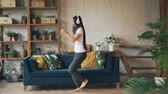 eğlenceli : Slow motion of cute Asian lady dancing and jumping on floor of modern apartment wearing headphones, holding smartphone and listening to music. Fun and youth concept. Stok Video
