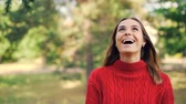 nevetés : Slow motion portrait of cheerful girl in warm sweater standing in the park with glad smile, laughing and looking at camera. Nature and millennials concept.