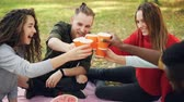 toasting : Slow motion of joyful girls and guys friends clinking glasses during picnic in park, young people are talking and laughing toasting holding drinks. Stock Footage