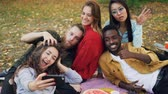 piquenique : Slow motion of joyful men and women taking selfie with smartphone and having fun lying on blanket in park in autumn. Picnic, nature and gadgets concept.