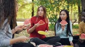 owoc : Slow motion of happy youth eating watermelon and talking on picnic in park sitting on blanket on meadow and enjoying fruit and leisure time. Food and nature concept. Wideo