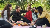 diverse : Slow motion of joyful friends African American and Caucasian doing high-five during picnic in city park. Friendship, healthy lifestyle and connection concept.