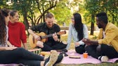 acústico : Slow motion of happy students playing the guitar and enjoying music in park on picnic in autumn, guitarist is playing while his friends are clapping hands. Vídeos