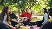 acústico : Slow motion of cheerful people singing and laughing while beautiful young woman is playing the guitar during picnic in park. Music, leisure and fun concept. Vídeos