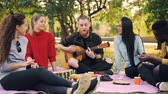 acústico : Slow motion of young man guitarist singing and playing the guitar outdoors on picnic while his friends are listening, laughing and clapping hands. Vídeos