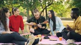 acústico : Good-looking guy is playing the guitar while his male and female friends are listening to music, singing and having fun on picnic in park. Friendship and culture concept.