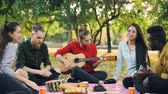 acústico : Pretty female guitarist is playing the guitar on picnic, her friends students are singing and clapping hands sitting on blanket in park. Open-air party and music concept.