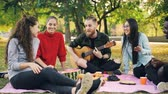 acústico : Multiracial group of friends is having fun in park playing the guitar and singing clapping hands enjoying leisure time and warm autumn day. People and music concept. Vídeos
