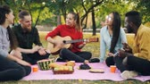 acústico : Multiethnic group of friends is singing in park and clapping hands while beautiful girl is playing the guitar on picnic. Food and blanket are visible.