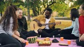 acústico : Cheerful African American man is playing the guitar for his friends sitting on blanket on picnic and enjoying warm autumn weekend. Leisure and music concept. Vídeos