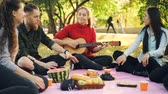 eğlenceli : Relaxing students are having picnic in park playing guitar singing songs and ejoying leisure time outdoors with friends. Food on blanket and nature is visible.