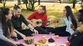 acústico : Pretty young lady is playing guitar while her friends are singing and listening to music resting on plaid in park. Food fruit and pastry are visible on blanket.
