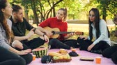 развлекательный : Romantic young people are singing and playing the guitar on picnic sitting on plaid on lawn in park and having fun. Musical instruments and culture concept.