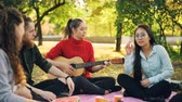 prato : Female guitarist is playing the guitar for joyful friends sitting on blanket on lawn in city park while guys and girls are listening, laughing and having fun.