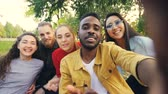 communiquer : Happy friends are making online video call looking at camera, talking and laughing while African American man is holding device with camera during picnic in park. Vidéos Libres De Droits