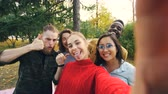 fotografia : Point of view shot of young woman holding device with camera and taking selfie with friends multi-ethnic group in park in autumn. Photography and people concept.