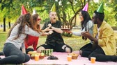 regozijo : Bearded man is celebrating birthday with friends in park blowing candles on cake shouting and expressing positive emotions while friends are laughing and clapping hands.