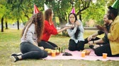 regozijo : Friends are congratulating Asian woman on birthday giving cake making surprise, girl is blowing candles, smiling and clapping hands during outdoor party in park.