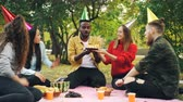 regozijo : Bearded African American guy is having birthday party in park blowing candles on cake and laughing enjoying surprise, his friends are clapping hands. Stock Footage