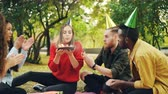 delightful : Beautiful girl in party hat is celebrating birthday with friends in park on picnic making wish, blowing candles on cake and having fun laughing. Events and nature concept.