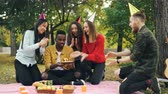 regozijo : Caring friends are bringing cake to African American man sitting on blanket in park on picnic with closed eyes, he is blowing candles and laughing enjoying surprise.