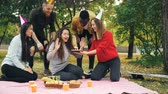 regozijo : Young people are congratulating girl on birthday bringing cake hugging and kissing her, woman is blowing candles, laughing and rejoicing during outdoor party in park.
