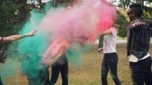 sale : Slow motion of happy students throwing colorful powder paint at each other at Holi festival laughing and having fun enjoying joyful tradition outdoors in park.