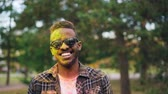 holi : Slow motion portrait of bearded African American guy in sunglasses, face and hair covered with powder paint at Holi festival. Man is looking at camera and smiling. Stock Footage