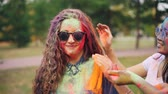 umírající : Slow motion of happy friends painting pretty girls face and hair with powder paint at Holi festival, woman is smiling and laughing wearing sunglasses. Dostupné videozáznamy