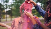 sale : Happy girls and guys are painting friend with bright colorful powder at Holi festival touching his face, hair and beard, young man in sunglasses is laughing.