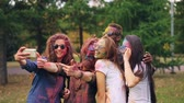 holi : Happy men and women friends with painted faces and hair are taking selfie at Holi festival using smartphone camera, people are posing and smiling. Fun and technology concept.