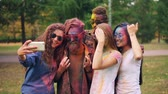 multicouleur : Slow motion of young people dirty with bright paint taking selfie in park using smartphone. Holi festival, modern technology and happy youth concept.