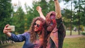 multicouleur : Girl and guy with faces and hair covered with paint are taking selfie together with smartphone standing outdoors in park and having fun enjoying party and technology.