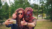 multicouleur : Slow motion of young beautiful couple man and woman taking selfie at Holi festival looking at smartphone camera and posing with hand gestures and tongue.