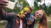 sale : African American guy wearing sunglasses is taking selfie with female friends at Holi color holiday, their faces and hair are dirty with multicolor paint. Vidéos Libres De Droits