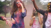 multicolore : Excited men and women are dancing at party covered with bright paint enjoying traditional Indian holiday Holi having fun and laughing. Nature and culture concept.
