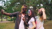 multicouleur : Slow motion of African American man in sunglasses taking selfie with pretty girls at Holi festival, their faces, hair and clothing are covered with paint.