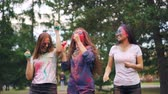 multicolore : Slow motion of cheerful girls multi-ethnic group dancing then throwing paint powder at outdoor party in park. Youth culture, happy people and fun concept.
