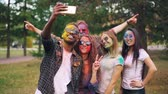 delightful : Slow motion of happy students multiethnic group with coloured faces and hair taking selfie in park using smartphone camera and having fun at Holi festival. Stock Footage