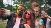delightful : Excited friends girls and guys are taking selfie with colored faces and hair using smartphone, stylish young man is jumping and laughing. Modern technology and party concept. Stock Footage