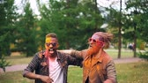 multicouleur : Two bearded guys with colorful faces covered with paint are dancing on lawn in park jumping and smiling enjoying party. Men with cool hairstyle are wearing sunglasses. Vidéos Libres De Droits